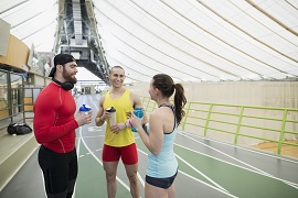 Runners resting talking drinking water on indoor track